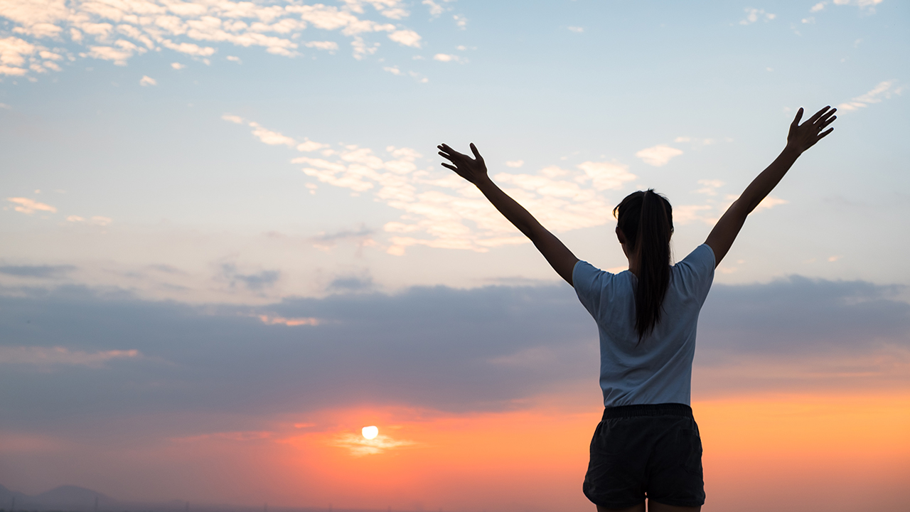 Woman looking at sunset feeling positive